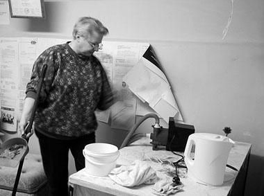Первый потоп в подвале. Редактор «ПТЖ», профессор СПбГАТИ, декан театроведческого факультета Е. Третьякова вникает в устройство насоса для откачивания талых вод. 2003 г. Фото М. Дмитревской